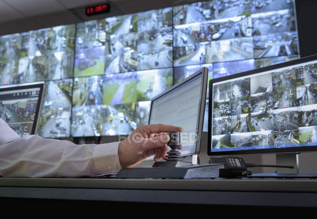 Detail of hand on camera control joystick in control room with video wall — Stock Photo