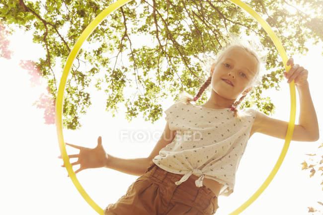 Низький кут зору переглядаючи Хула Хооп в камеру посміхається дівчина — стокове фото