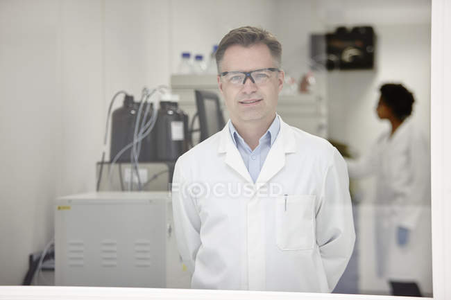 Scientist smiling in laboratory, colleague working in background — Stock Photo