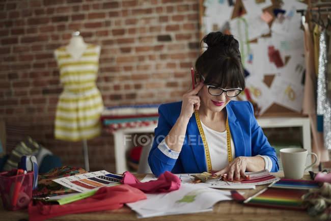 Frau im Designstudio sitzt am Schreibtisch, Hand auf Kopf mit Blick nach unten — Stockfoto