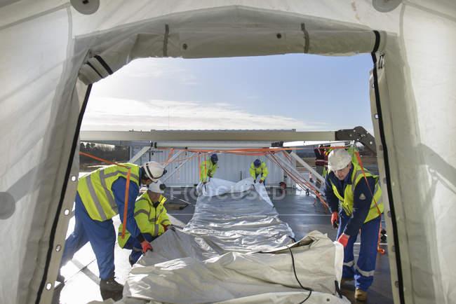 Сотрудники аварийно-спасательной группы возводят палаточный центр управления — стоковое фото
