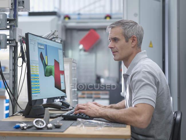 Ingeniero observando el progreso de Cnc lathe en la pantalla de la fábrica ortopédica. - foto de stock