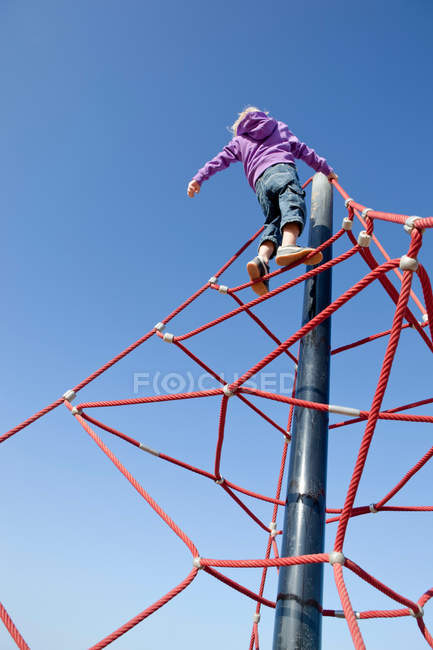 Low angle view of Boy climbing junglegym — Stock Photo