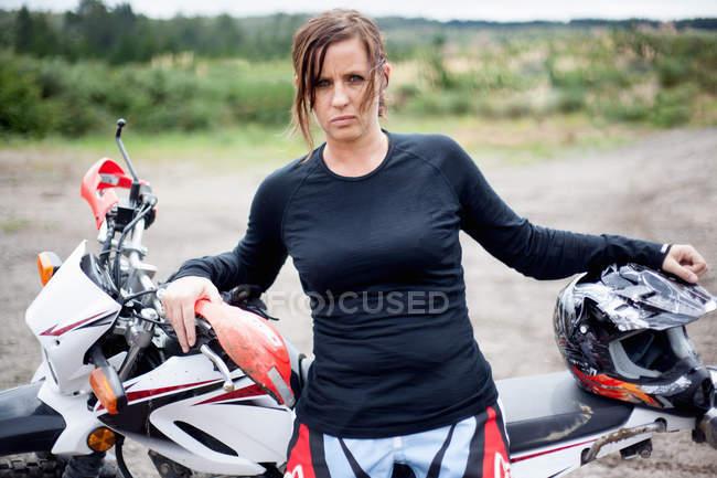 Портрет молодого дорослого жіночого мотоцикліста спираючись на мотоциклі — стокове фото