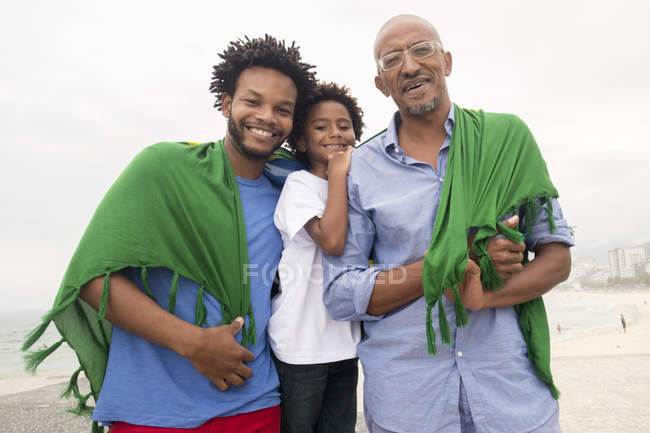 Mid adult man with father and son wrapped in Brazilian flag on Ipanema beach, Rio De Janeiro, Brazil — Stock Photo