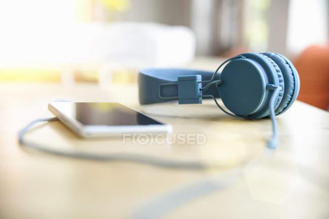 Casque bleu attaché au smartphone sur la table — Photo de stock