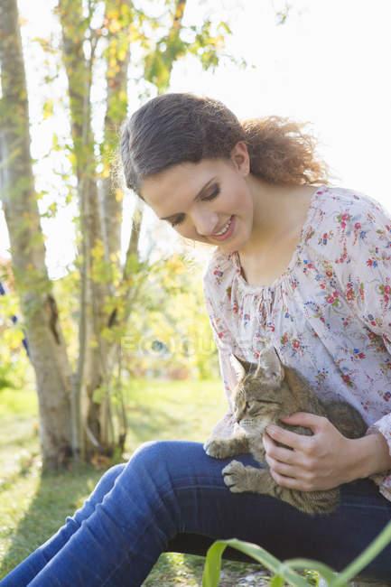 Teenage girl relaxing in garden petting cat — Stock Photo
