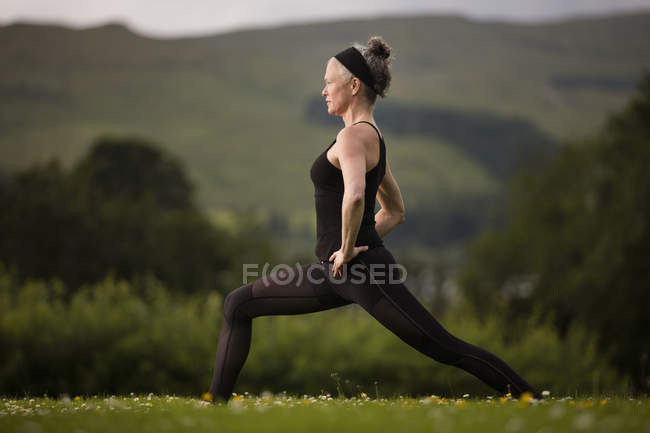 Mature woman practicing yoga warrior pose in field — Stock Photo
