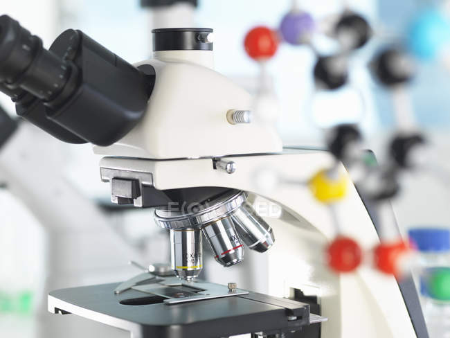 Microscope viewing sample with a ball and stick molecular model illustrating ground breaking research — Stock Photo