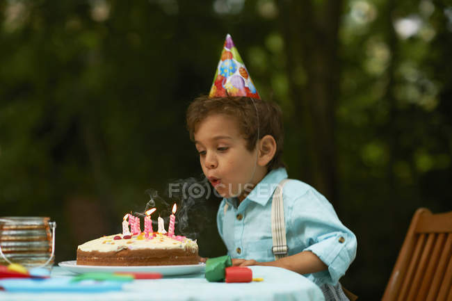 Boy blowing candles on birthday cake at  garden birthday party — Stock Photo