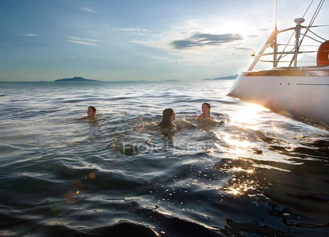 Three people swimming next to sailboat — Stock Photo