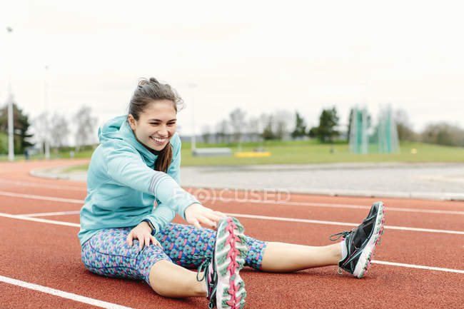 Young woman on running track, exercising, stretching — Stock Photo
