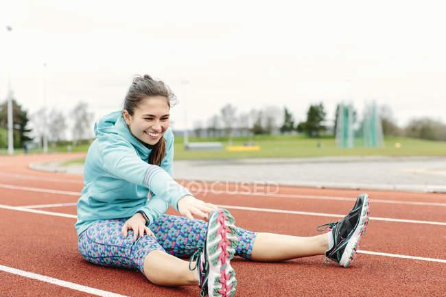 Молодая женщина на беговой дорожке, упражнения, растяжка — стоковое фото