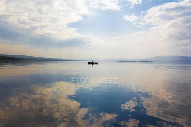Человек в лодке на озере — стоковое фото