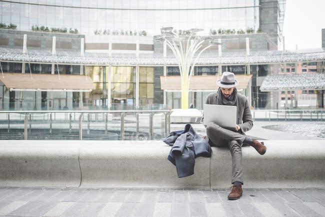 Businessman sitting on wall using laptop — Stock Photo