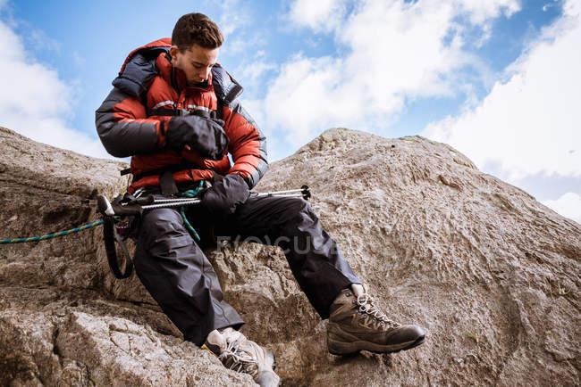 Joven escalador masculino en cuerda de control de roca, The Lake District, Cumbria, Reino Unido - foto de stock