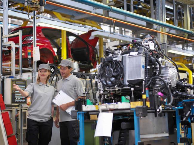 Lavoratori di impianti automobilistici con parti di auto — Foto stock