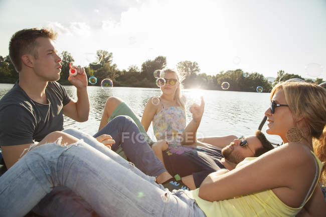Four young adult friends blowing bubbles on riverside pier — Stock Photo