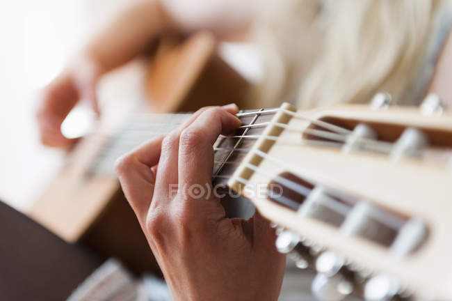 Hands of young woman playing acoustic guitar — Stock Photo