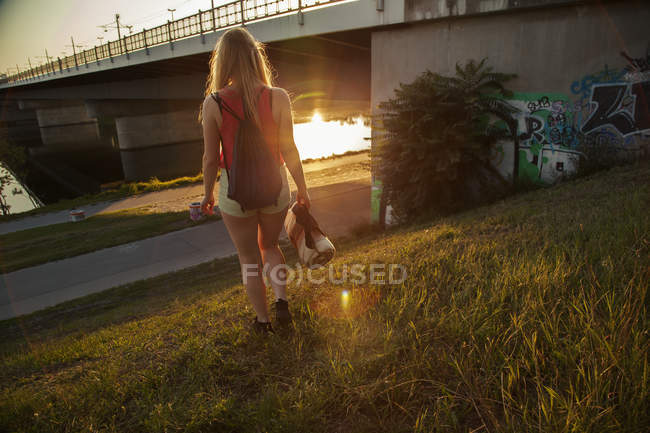 Rear view of young woman walking near bridge and riverside — Stock Photo