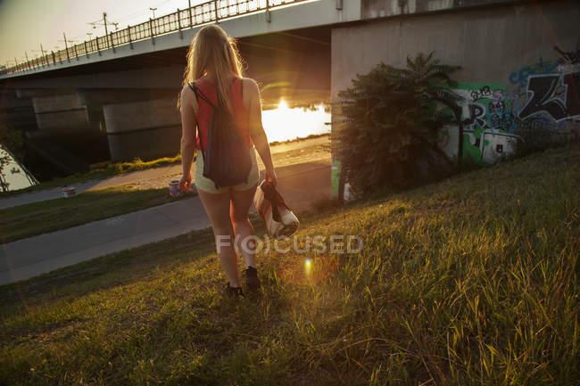Vue arrière du jeune femme marche près du pont et le bord de la rivière — Photo de stock