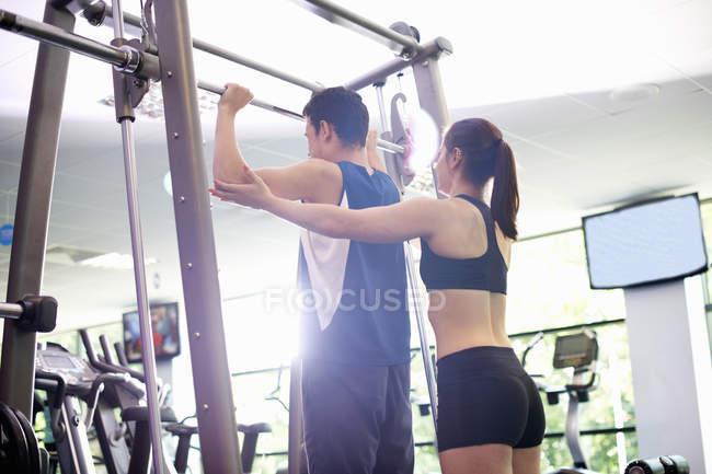 Личный тренер помогает юноше поднимать тяжести — стоковое фото