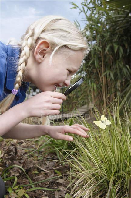 Крупный план школьницы, смотрящей на бабочку в саду — стоковое фото