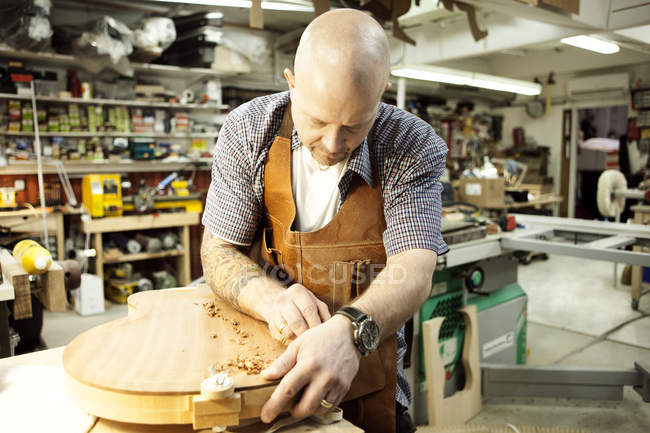 Guitar maker measuring wooden guitar shape in workshop — Stock Photo