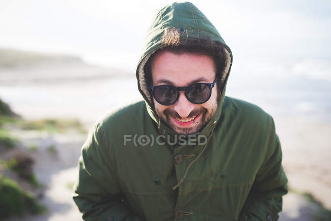 Portrait of mid adult man in hooded jacket at coast — Stock Photo