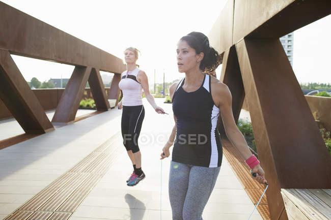 Дві жінки навчання з пропуску мотузки на міському мосту — стокове фото