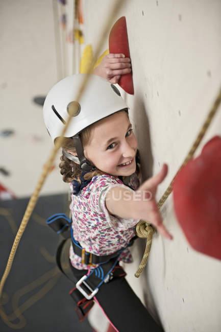 Дівчина, навчання, щоб піднятися з мотузок на скелелазіння стіна — стокове фото