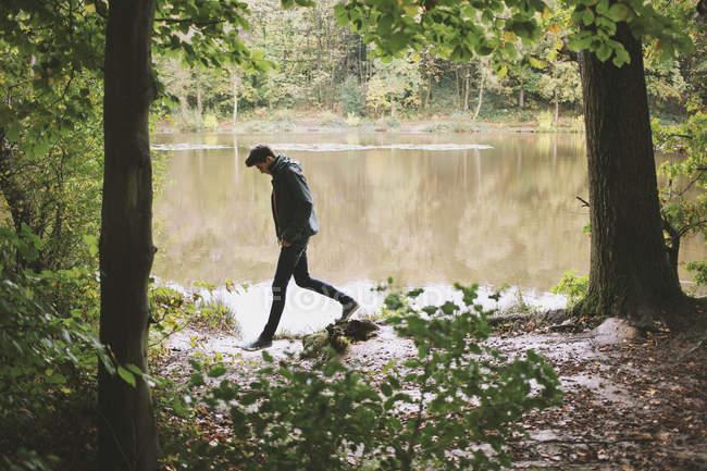 Silueta joven paseando por la orilla del río - foto de stock