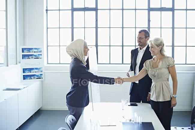 Молодая бизнесвумен пожимает руку бизнес-леди в офисе — стоковое фото