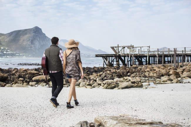 Coppia giovane che passeggia sulla spiaggia portando la chitarra, Città del Capo, Western Cape, Sudafrica — Foto stock