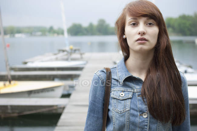 Portrait of serious young woman by lake — Stock Photo