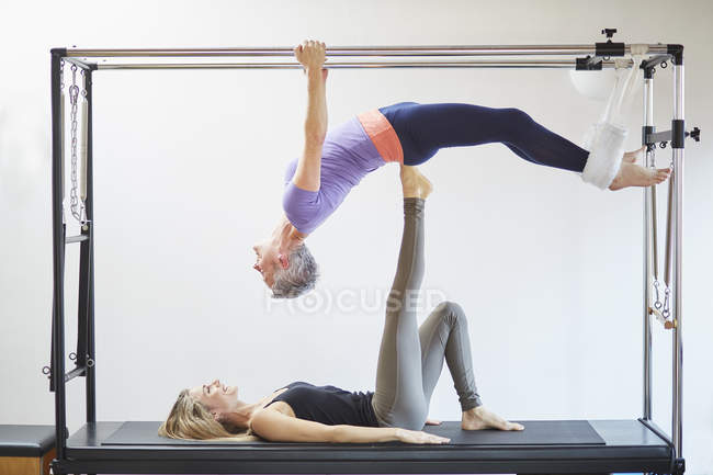 Two mature women practicing pilates on trapeze table in pilates gym — Stock Photo