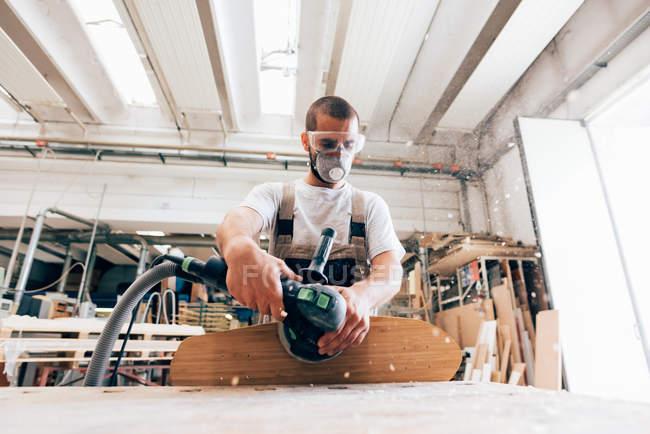 Mann schleift Skateboard in Werkstatt — Stockfoto