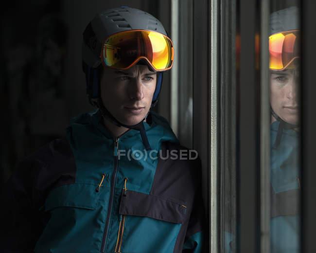 Человек в шлеме и лыжных очках смотрит в окно — стоковое фото