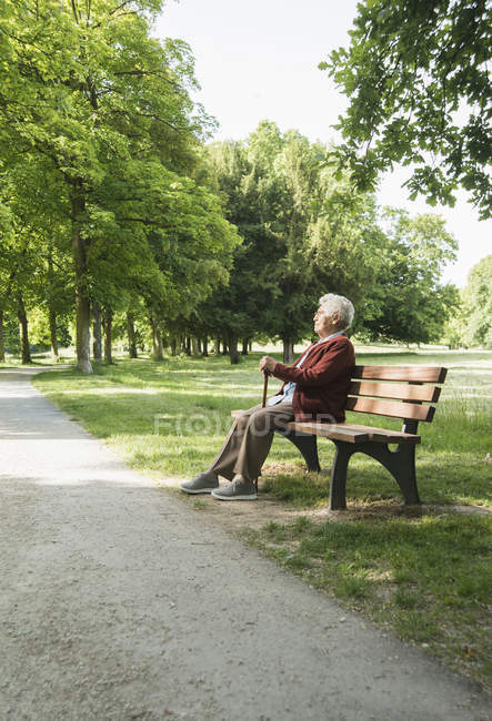 Senior woman sitting on park bench in park — Stock Photo