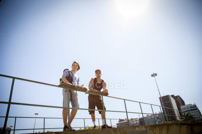 Двое мужчин, держа скейтборды, опираясь на перила, низкий угол зрения — стоковое фото