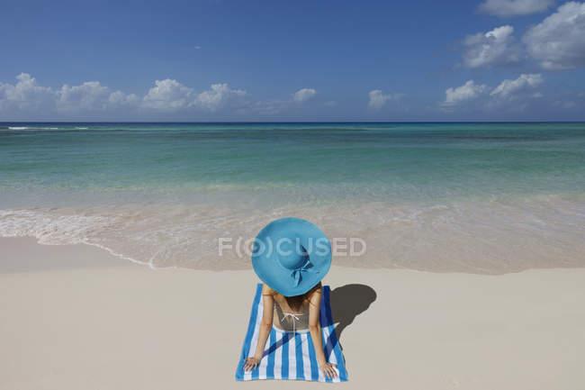Jovem mulher relaxante na praia com chapéu azul — Fotografia de Stock