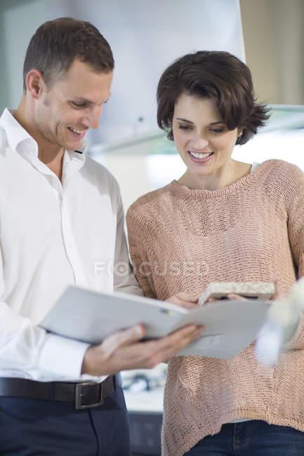 Venditore e cliente donna guardando brochure in showroom cucina — Foto stock