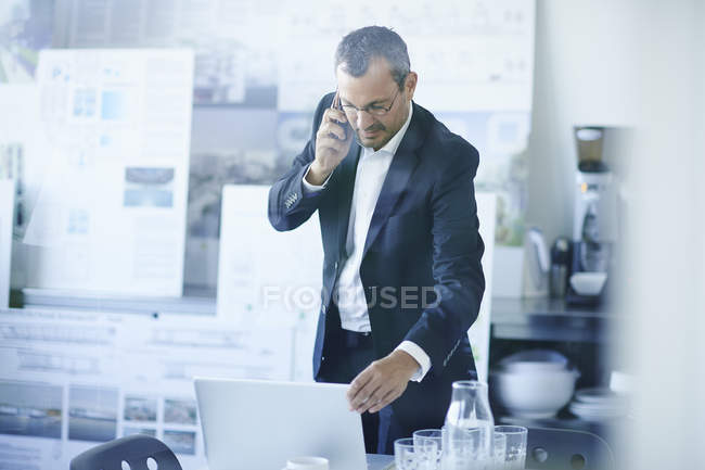 Business man chatting on smartphone whilst using office laptop — Stock Photo