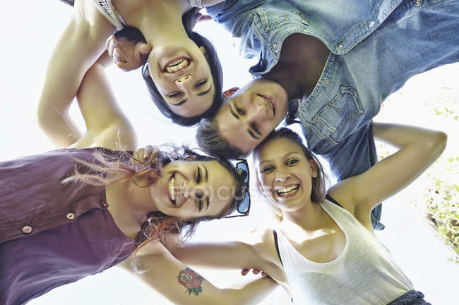 Group of friends in huddle smiling, low angle view — Stock Photo