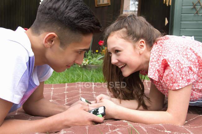 Pareja adolescente con teléfonos inteligentes acostados en una manta en el jardín - foto de stock