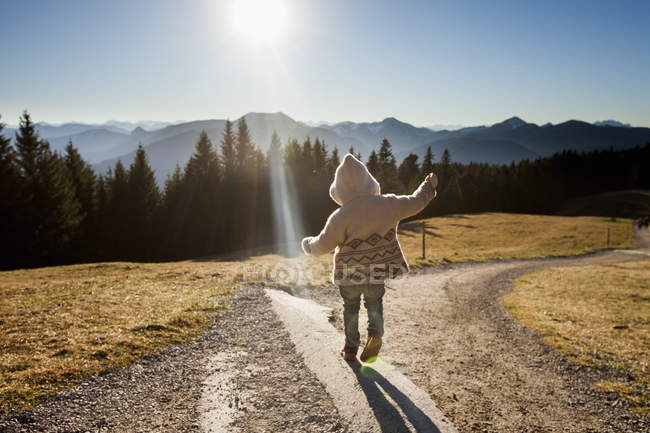 Rear view of female toddler toddling on sunlit dirt track, Tegernsee, Bavaria, Germany — Stock Photo