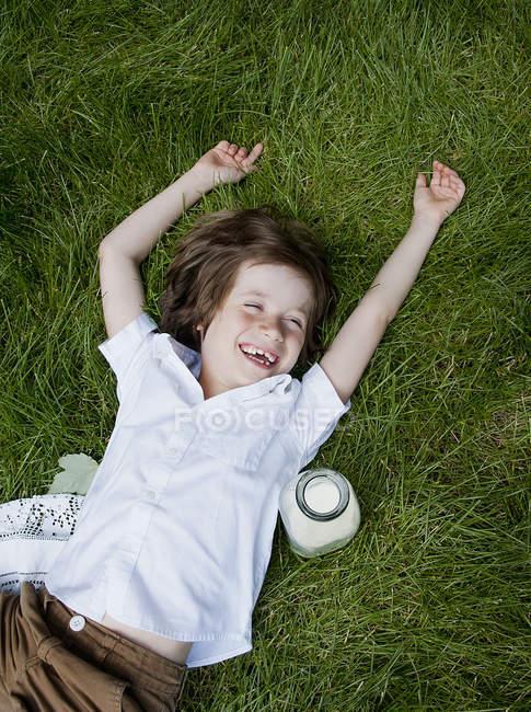 Мальчик лежит на траве с поднятыми руками и смеется — стоковое фото