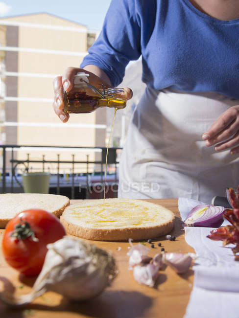 Cropped image of woman pouring olive oil on bread at kitchen counter — Stock Photo