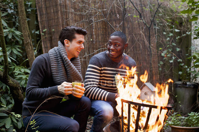 Two young men crouching in front of garden fire with coffee — Stock Photo