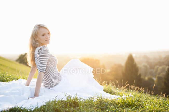 Giovane donna che si siede su Parco collina guardando — Foto stock